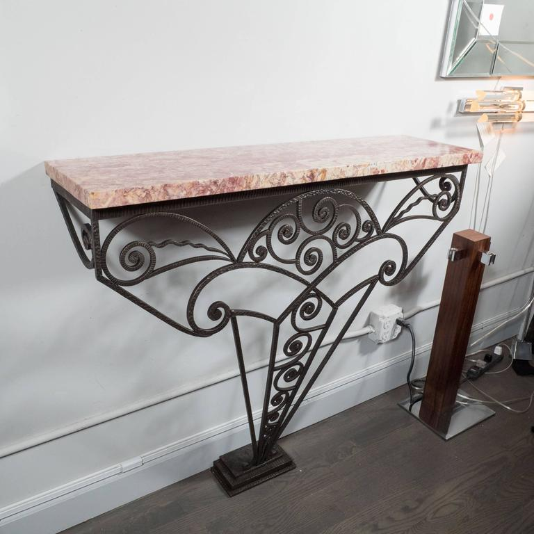 An Art Deco wall-mounted console in the manner of Edgar Brandt, the base on this console is an elaborate geometric amalgamation of wrought iron scrolls and arches branching out to support an exotic marble top in tones of fuchsia, rose and ivory. The