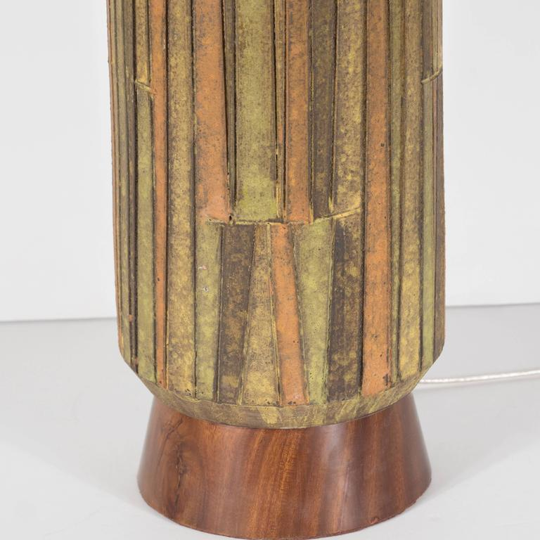 This Mid-Century Modernist earth-toned ceramic and walnut table lamp was handmade in the United States by the esteemed maker Raymor, circa 1960. A subtly conical hand-rubbed walnut base supports a ceramic body composed a mosaic of earth-tone ceramic