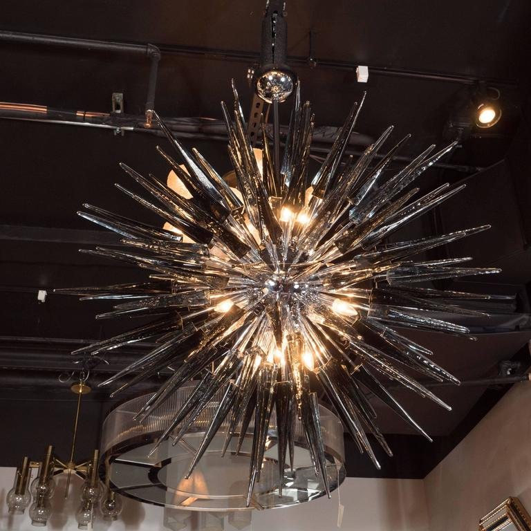 This stunning smoked grey Murano glass spiked starburst chandelier was handblown in Italy circa 2000. It features an abundance of spiked rods emanating from its center in alternating lengths, giving its overall form a staggered multi-dimensionality.