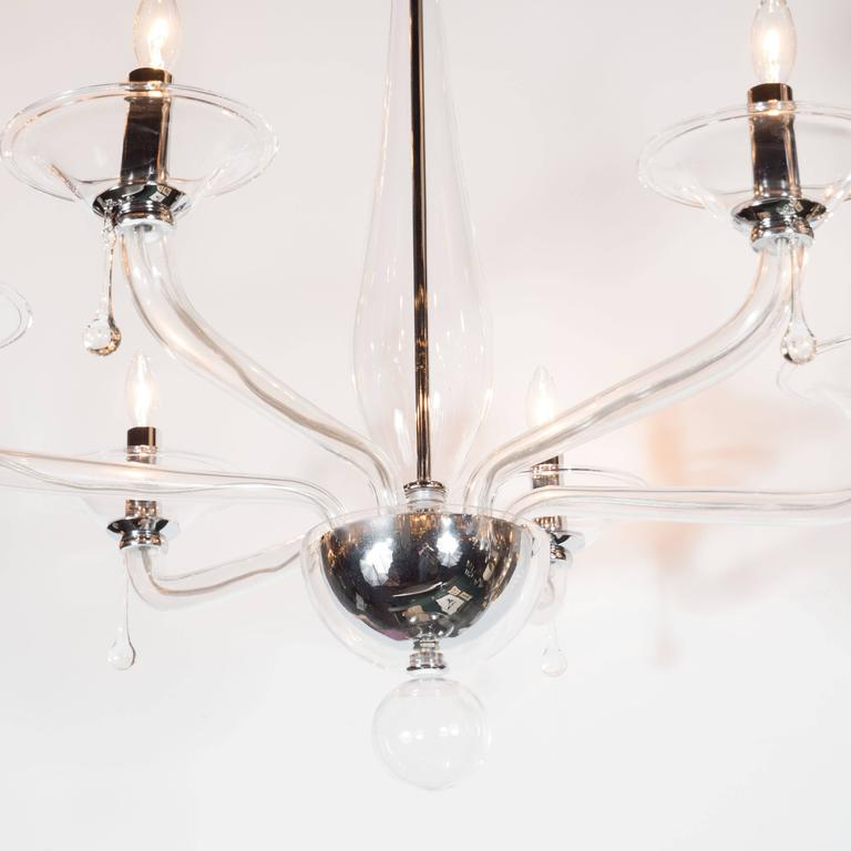 A Mid-Century modernist handblown Murano chandelier featuring six arms of clear glass. A hollow glass ball hangs from the bottom, which is supported by a reverse half-dome. Six independent, upward-curved arms with bowl shades each hold a standard