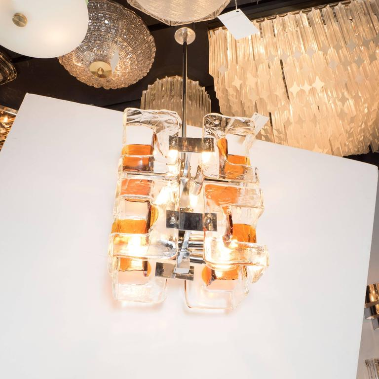 This super chic chandelier features interlocking geometric glass pieces in handblown Murano glass by Mazzega. They are in clear and smoked amber. The glass is thick and extremely high quality. The frame is polished chrome and fitted for eight
