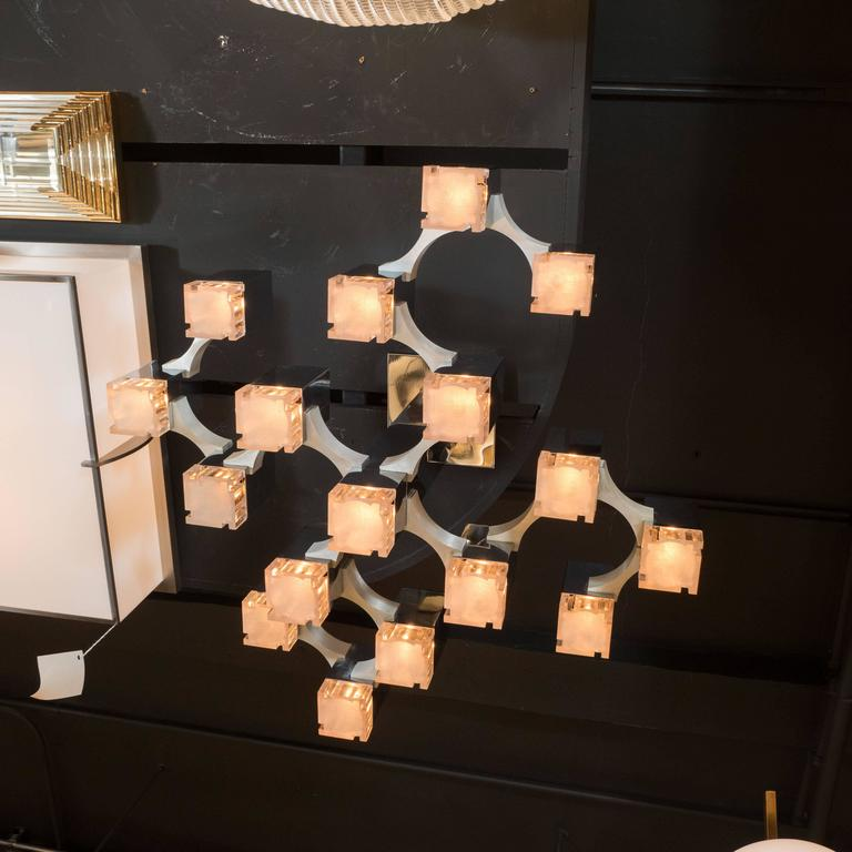 A Mid-Century modernist cube chandelier in chrome and brushed aluminium by Gaetano Sciolari. 18 staggered chrome cubes at differing heights with textured lucite shade covers make-up this sculptural piece of Italian lighting, all connected in a
