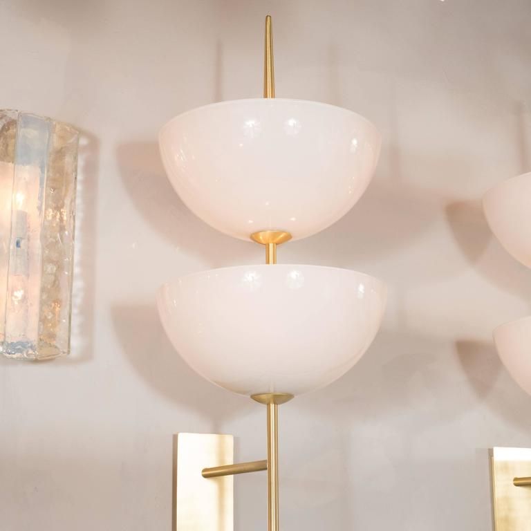 A pair of reverse-dome trophy sconces in milk glass and polished brass. Rectangular back plates support a brass spear-shaped arm with two floating reverse-dome milk glass shades, each housing a pair of up to 60W Edison-based sockets, totaling four