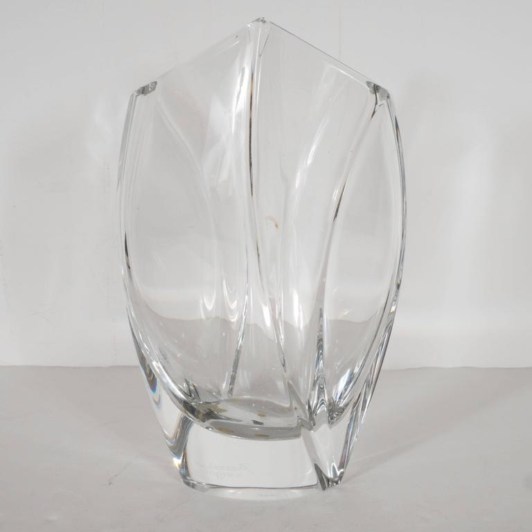 This gorgeous vase was designed by the illustrious French designer Robert Rigot and realized by Baccarat- arguably the world's premiere crystal maker, circa 1980. It features modernist curved forms cut into the glass and a sloped top that comes to