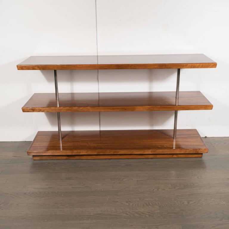 This elegant Art Deco skyscraper style piece by Gilbert Rohde features book-matched Acacia shelves circumscribed by walnut on the perimeter with brushed aluminium rods supporting the structure. It represents an important (not to mention stunning)