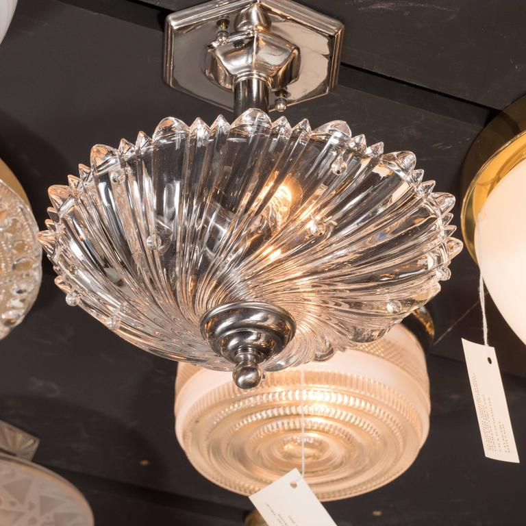 This modernist semi-flush mount features a dynamic whirlpool design in translucent glass with round glass bead embellishments protruding from the heavily textured surface. The fixture attaches to a skyscraper style octagonal base in polished nickel