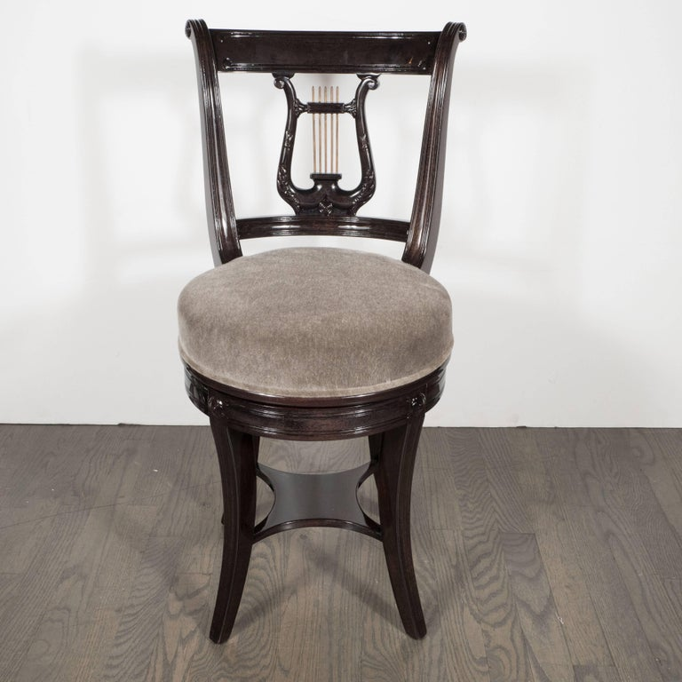 This whimsical stool or vanity chair was realized in America, circa 1940. A stylized lyre, with brass spindles, forms the back of the chair. The apron that supports the dove gray mohair seat features stylized floral details and a reeded design. This