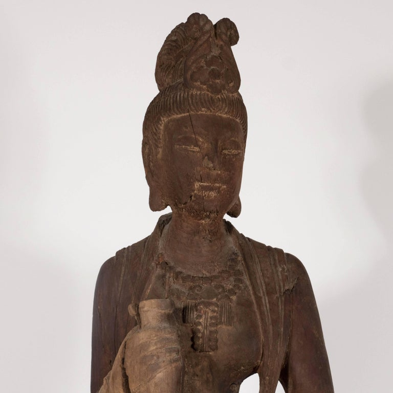 This beautiful sculpture realized in China in the 18th century depicts Guanyin, a Bodhisattva associated with compassion. The female form holds a pot in her hands. She appears draped in a long flowing dress with a tiara- the many details of her