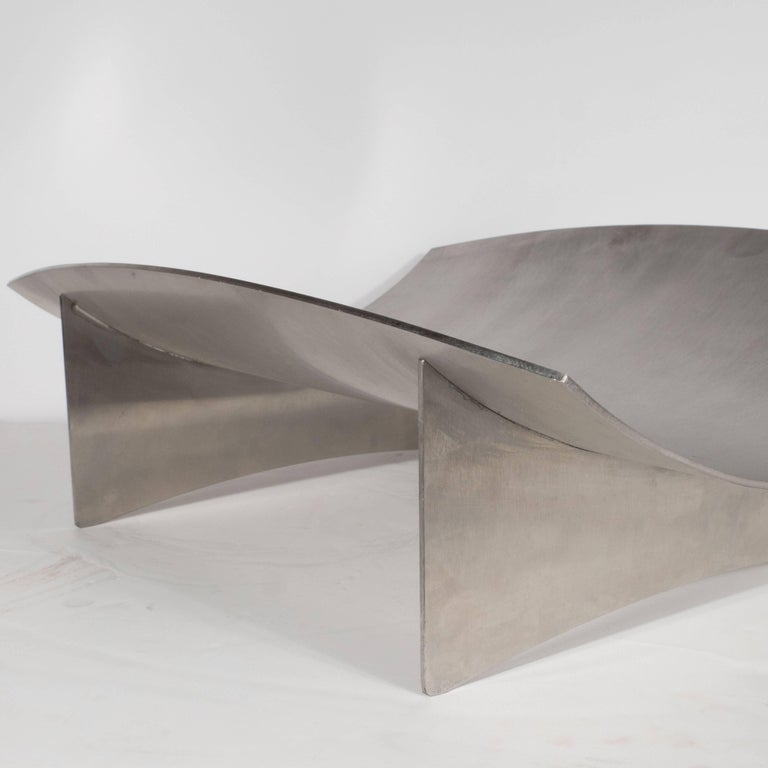 This sophisticated log holder was realized from brushed aluminum in Denmark, Circa 1950. While it is a perfectly functional log holder, it is also a compelling object. Its undulating top and crested base embody the organic curvilinear lines that