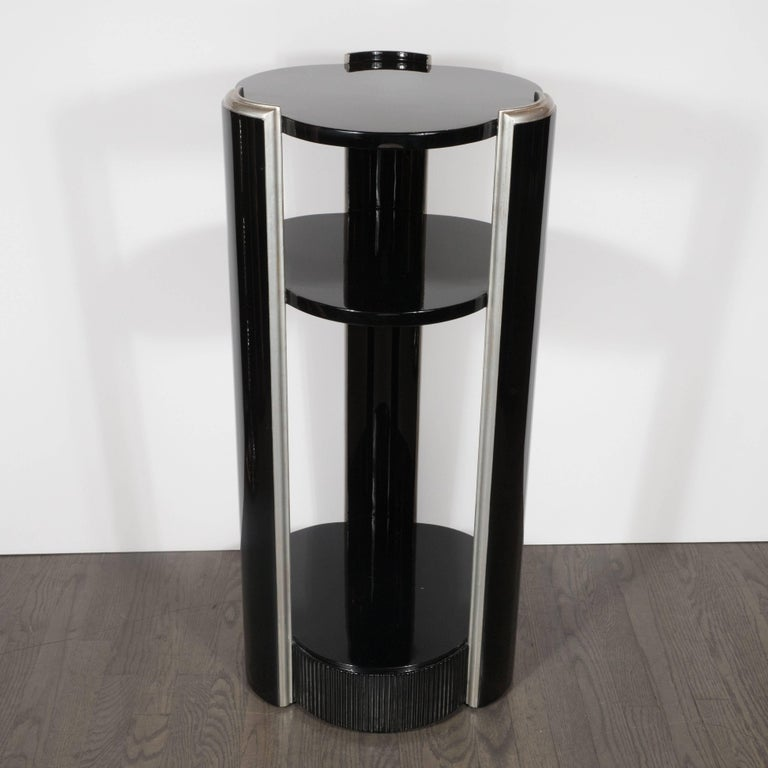 This refined black lacquer pedestal features three clover shaped tops, resembling Van Cleef & Arpels