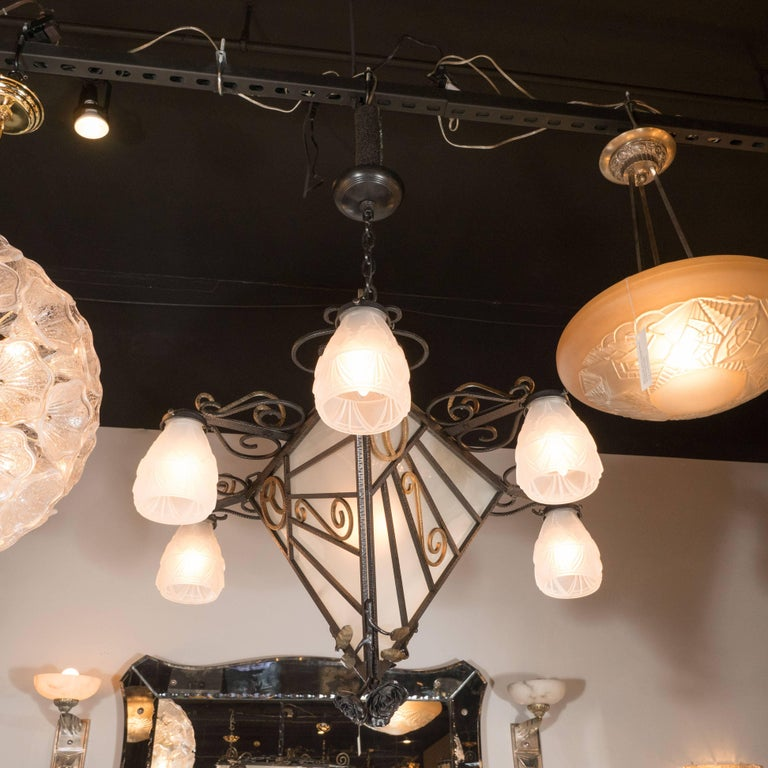 This exceptionally fine wrought iron chandelier was produced in France, circa 1930, at the height of Art Deco. With its stylized sunburst wrought iron design and heirloom rose finial, this piece exemplifies the exquisite finishes and exacting