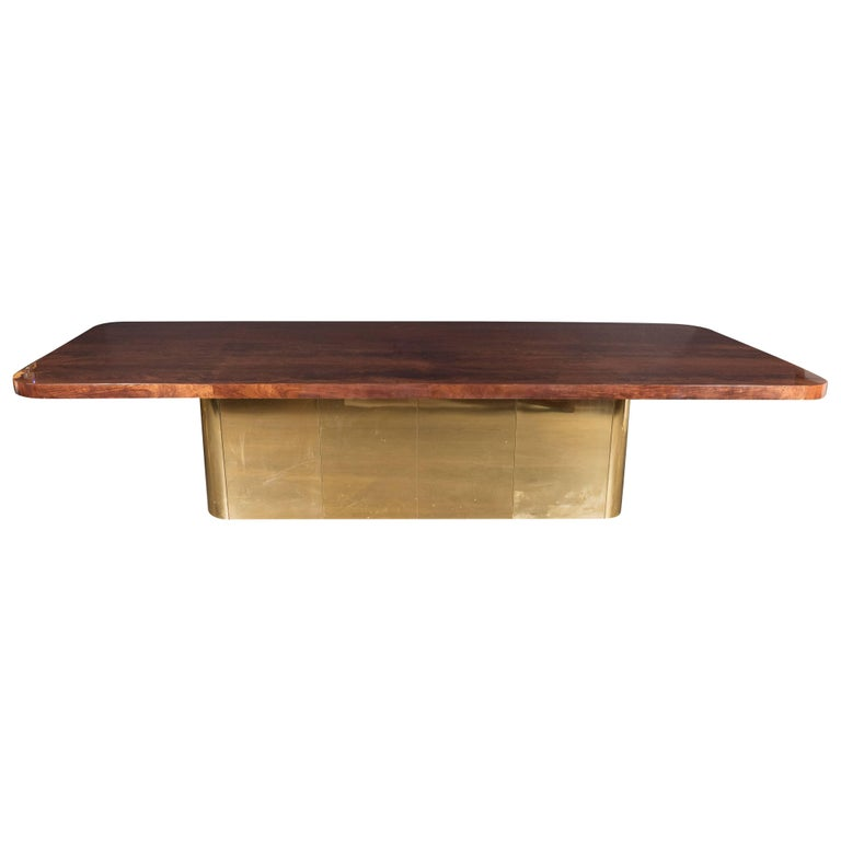 This monumental Mid-Century Modern dining table has a top constructed from gorgeous burled and bookmatched walnut and a rectangular streamlined form base with rounded edges in brass, creating a stunning material contrast to the woodgrain. This