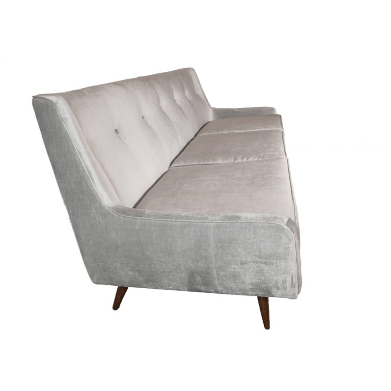 This refined Mid-Century Modern button back sofa was realized in the United States, circa 1960. It is supported by six conical tapered legs in hand rubbed walnut, three plush cushions and gently curved armrests. With its economy of form and clean