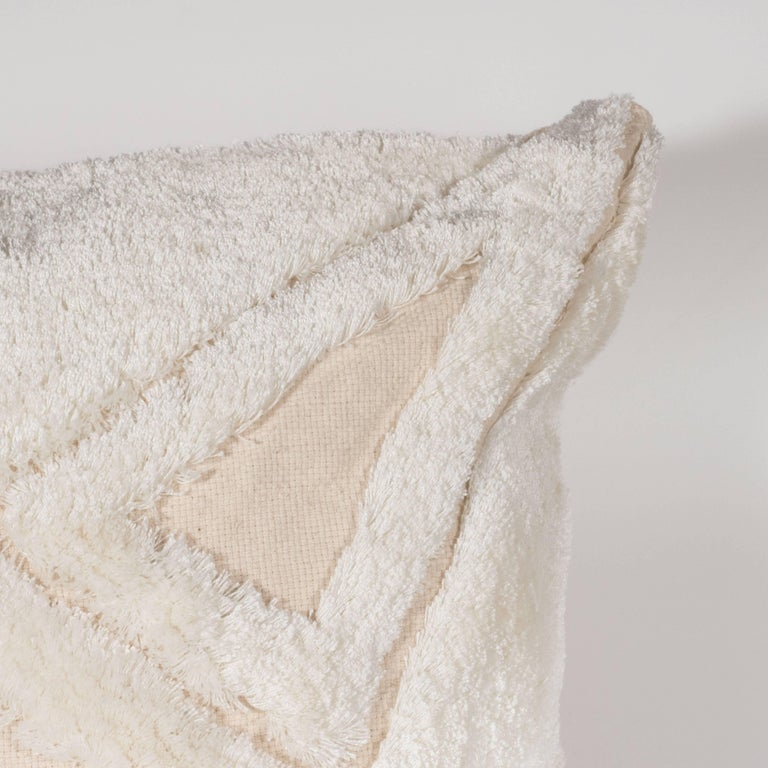 This elegant and understated pillow was artisanally crafted in the United States from Fine imported cotton in a cream hue. It features a diamond form in the center with triangles emanating outward from each side, all realized in a long white thread
