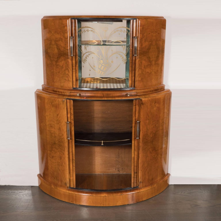 This Art Deco streamlined Skyscraper style tambour bar cabinet was realized in the England, circa 1935. It offers a tiered demilune form with two spacious compartments. The lower compartment has a black enamel shelf with a brass rail, while the