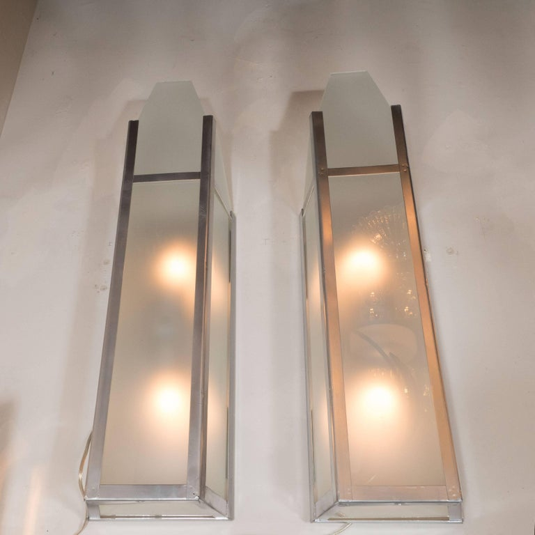 This sophisticated pair of sconces originally hung in the in the iconic Tower Theatre in Chicago. They features a rectangular form with frosted glass shades supported by a polished aluminum frame. With their skyscraper style design and industrial