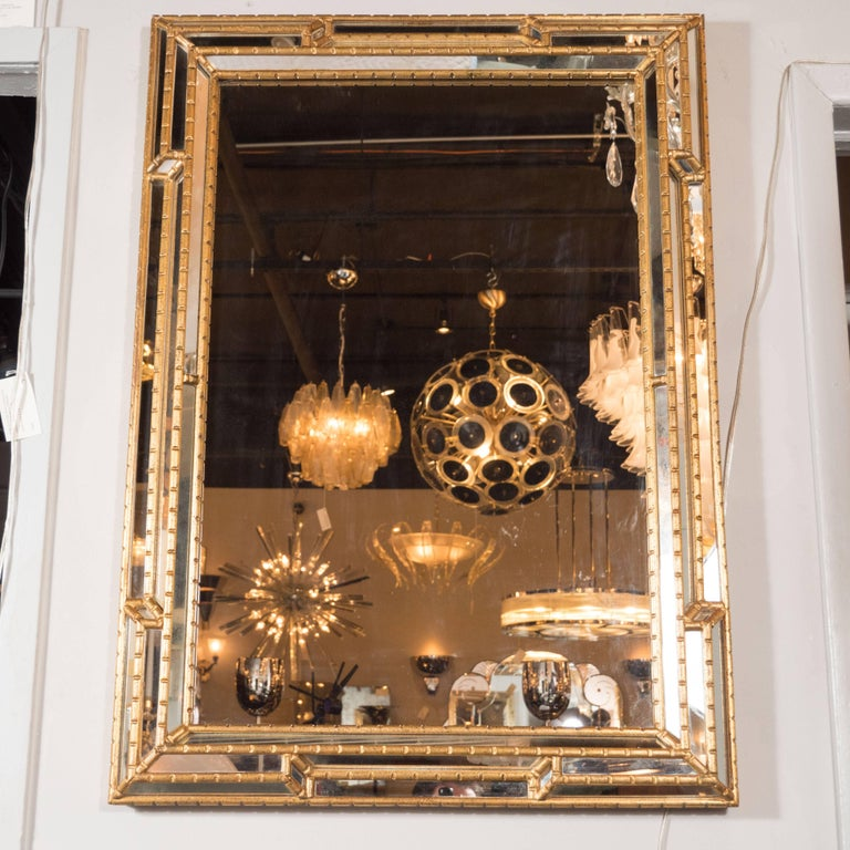 This dramatic and sophisticated mirror was realized in the United States, circa 1970. The border is composed of three channels of mirrored glass separated by gilded and ribbed bamboo with embedded geometric forms- namely rectangles and diamonds.