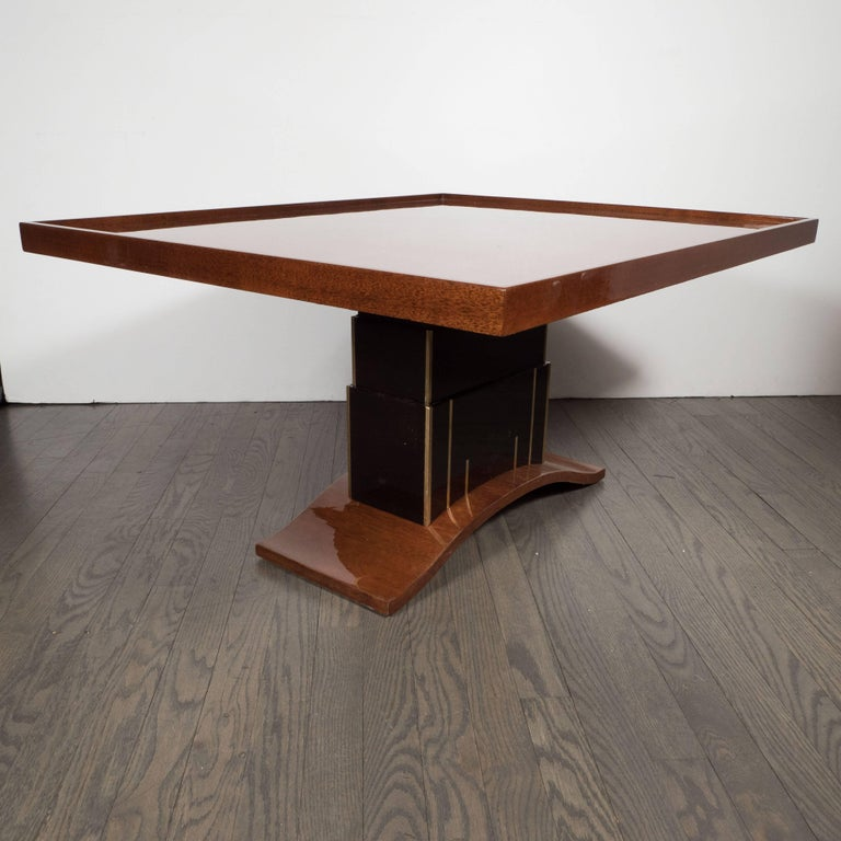 This stunning Art Deco skyscraper style occasional table was realized in the United States, circa 1935, at the height of Art Deco. It features a top consisting of walnut with a bookmatched mahogany border and a raised perimeter. The skyscraper style