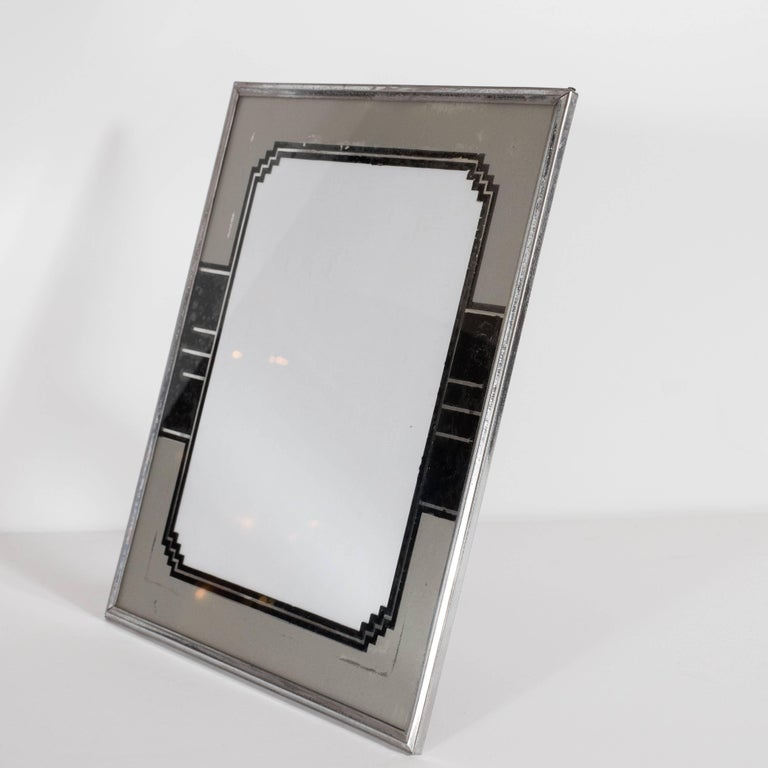 This stunning skyscraper style picture frame was realized in the United States, circa 1935. It features a geometric reverse painted border and three lines of varying lengths extending from the sides that suggest a cityscape. This piece exhibits a