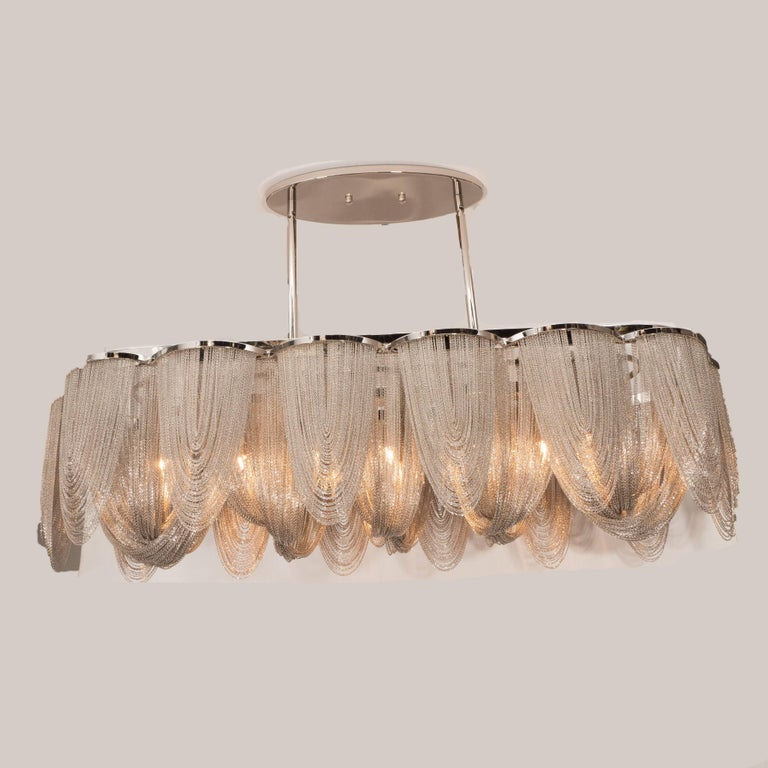 This stunning and sophisticated chandelier, realized in the style of Barlas Baylar, is composed of an abundance of draped stainless steel chains suspended from demilune supports. These supports extend from a streamlined ovoid body which suspended