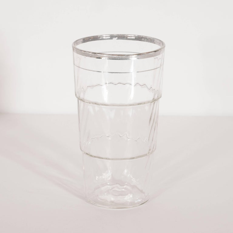 This elegant set of four glasses were realized in the United States, circa 1935. They offer a skyscraper style design composed of three tiers of ascending diameter in textured glass with subtle raised angular ridges that suggest a chevron pattern.