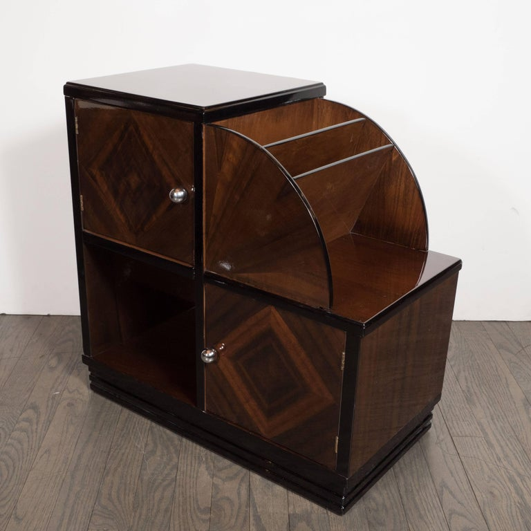 This stunning magazine stand was realized in the United States, circa 1935. It offers two cabinets with chrome pulls arranged caddy corner connected a square cut-out compartment on bottom and a demilune form on top with two shelves. There are two