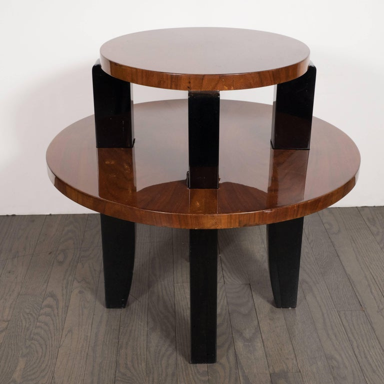 This stunning two-tier occasional/ side table was realized in France, circa 1935. It features two circular tiers composed of bookmatched walnut attached with black lacquer saber style legs. This piece showcases the understated and refined beauty of