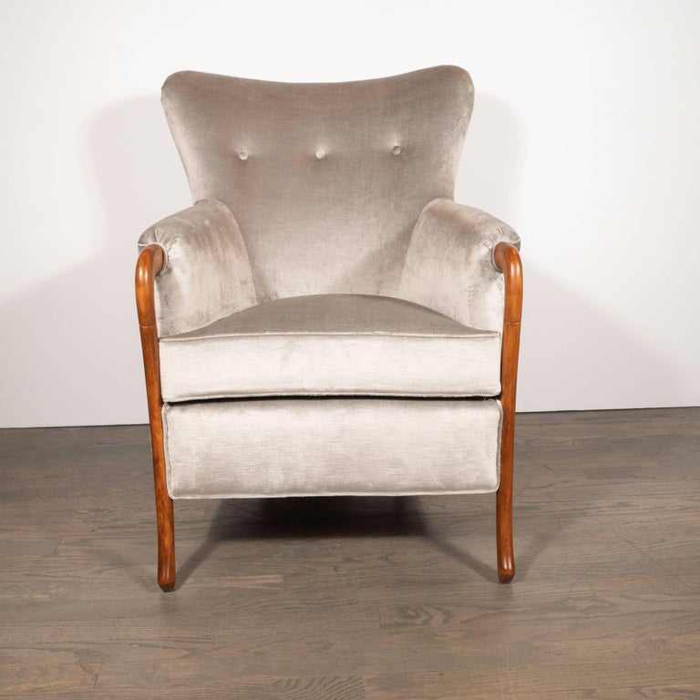 This refined and stately arm Mid-Century Modern armchair was realized in the United States, circa 1950. It features sinuously curved scroll form front legs that attach to the angled arm rests and shorter back legs with protuberant ends in walnut
