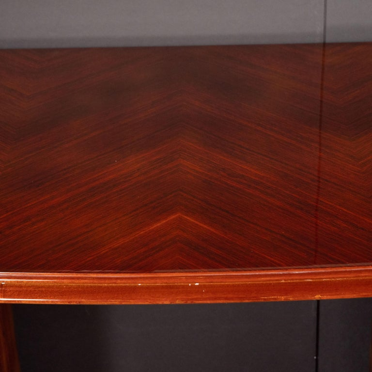 This elegant and refined Art Deco desk was realized in France, circa 1935. It features a gently curved bowfront rosewood top with a skyscraper style stepped perimeter, whose inherent grain has been bookmatched to create chevron patterns throughout.