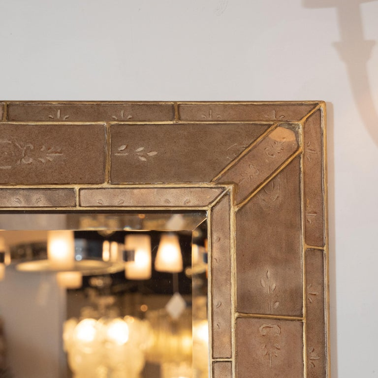 This sophisticated shadowbox mirror was realized in the United States, circa 1950. It offers a shadwobox plinth form with angled sides consisting of a mosaic of a rectangular forms in hand-painted smoked bronze pigment. The panels are adorned with