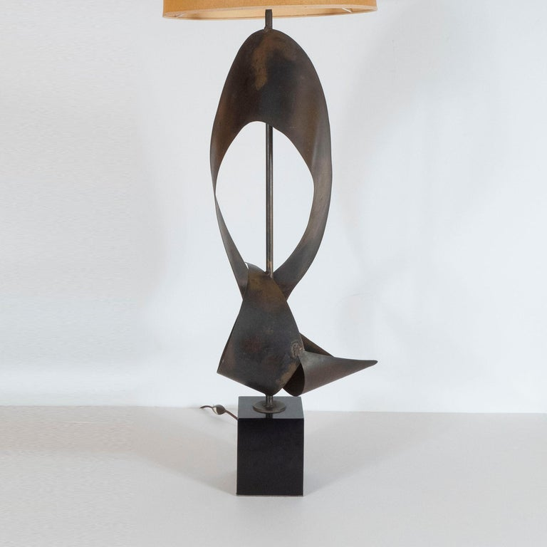 This dramatic and graphic pair of table lamps were realized in the United States, circa 1960. They feature contorting ribbons of patinated steel threaded with a cylindrical rod in the same material that attaches to a volumetric square black enamel