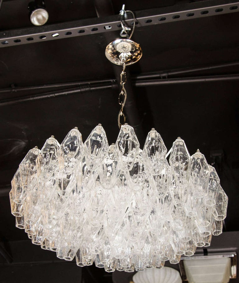 This luminous modernist glass chandelier features numerous handblown Murano translucent glass polyhedral shades. Each glass polyhedral shade is individually hung from its frame by hand. The frame features the subtle upward graduation from its centre