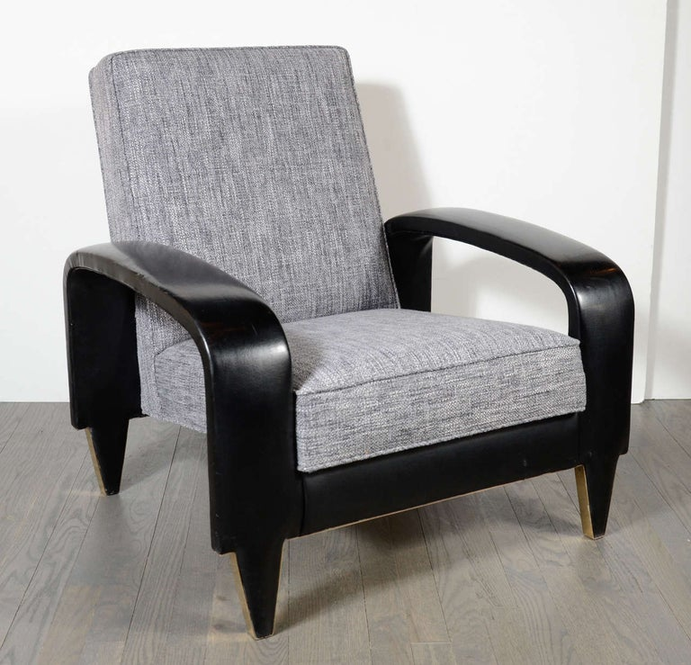 This rare Art Deco club chair features sculptural banded upholstered leather arms and new woven grey and pearl tweed upholstery. It has tapered legs with brush brass details and came from an Italian cruise liner.