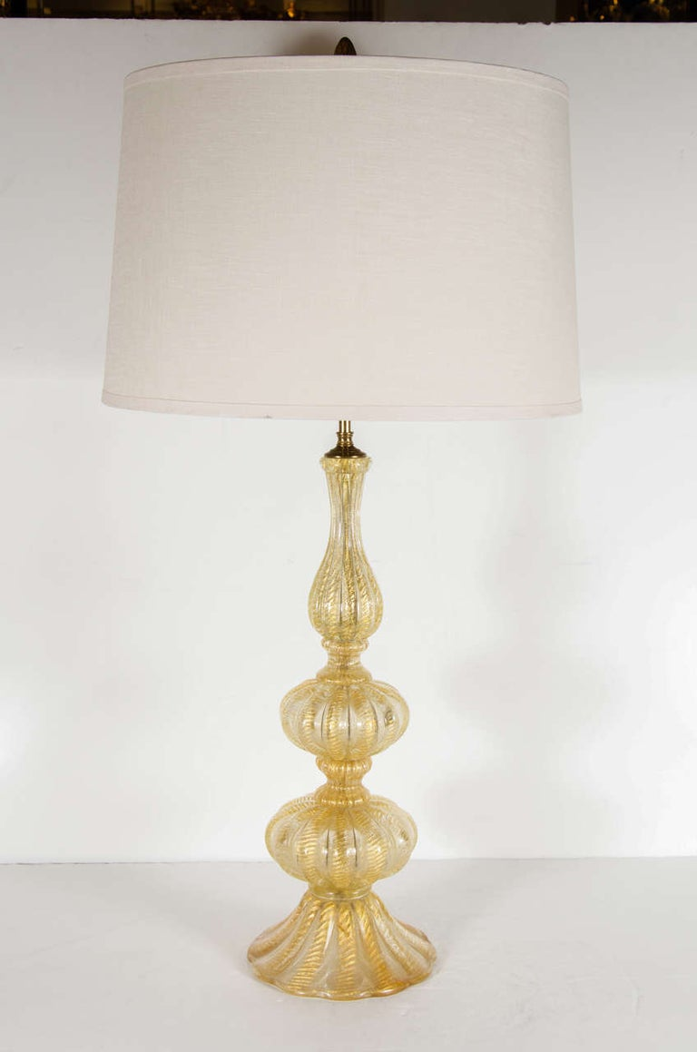 This elegant Mid-Century Modern table lamp was hand-blown in Murano, Italy by the esteemed studio Barovier e Toso, circa 1950. It offers a reeded undulating form consisting of stacked ovoid forms- separated by fluted hourglass shaped embellishments-