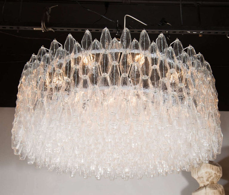 This stunning modernist chandelier is hand blown in Murano, Italy- the island off the coast of Venice renowned for centuries for its superlative glass production. It consists of numerous polyhedral shades suspended from a lustrous chrome body in a
