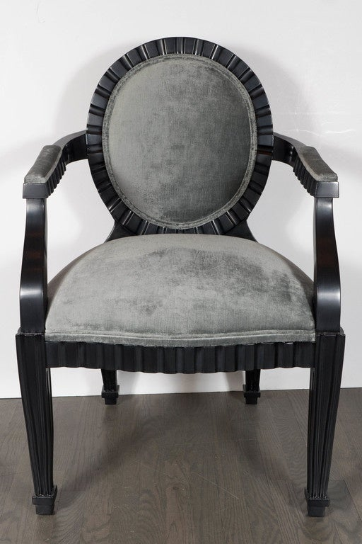This stunning pair of Mid-Century Modern chairs were realized by the esteemed designer Donghia in the United States, circa 1980. They feature Ebonized Walnut bodies with circular backs, conical legs and scalloped channel detailing that runs around