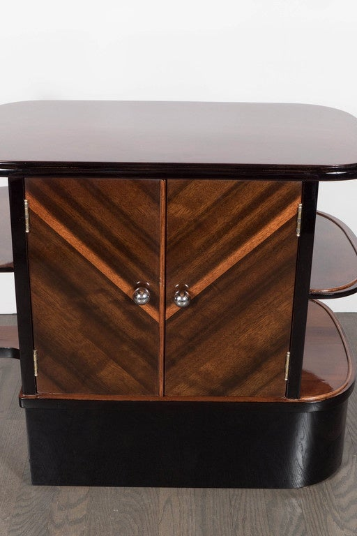 Streamlined Art Deco end table / dry bar cabinet in book-matched exotic Walnut with black lacquer accents and chromed ball pulls.  This exquisite cabinet features a thick banded base of black lacquer with a two door cabinet top with an open interior