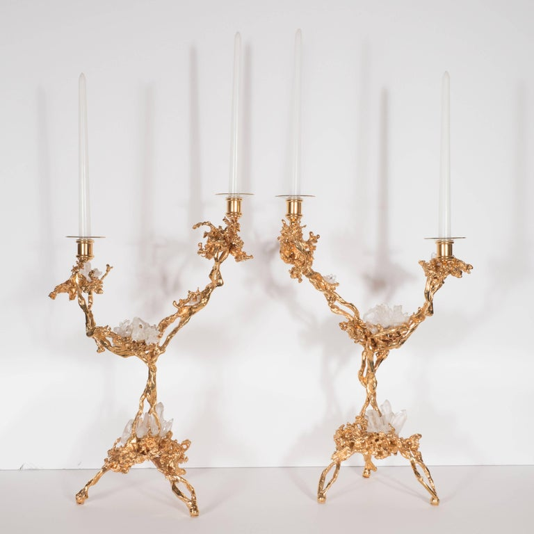 This stunning pair of Mid-Century Modern candlesticks were realized in France, circa 1970 by the esteemed artisan Claude Victor Boeltz. They offer an exploded form sculpted, by hand, and cast in bronze, consisting of two arms and three feet plated