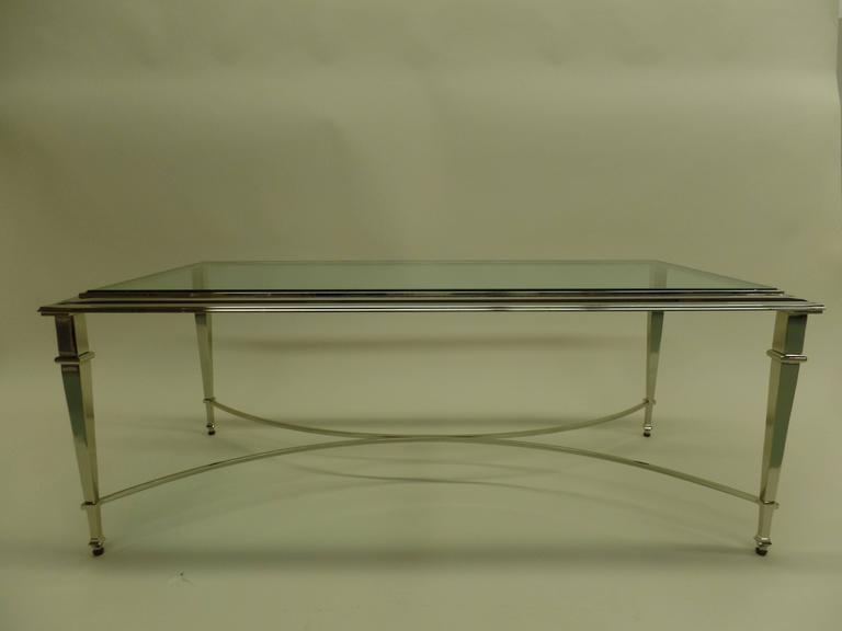 Elegant, timeless French Mid-Century Modern Style Cocktail table in the Neoclassical Spirit of Maison Ramsay.  The piece is delicately nickeled with stunning, tapered legs united by an X-frame stretcher. The top is raised, characteristic of Ramsay
