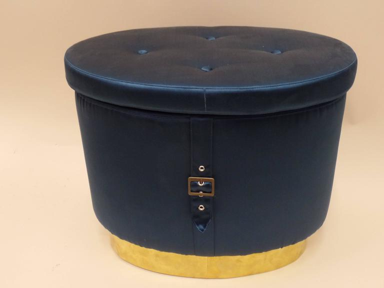 Stunning pair of Italian 1970s oval form stools, ottomans, poofs or benches with a recessed brass base, tufted silk seats and a belt with brass buckle that forms a crest on the central apron!