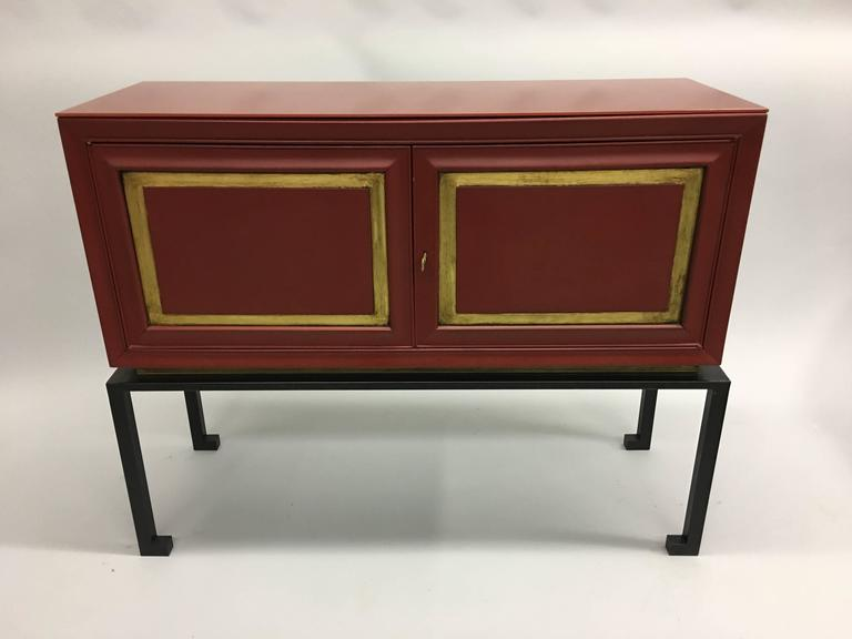 Two unique, elegant modern neoclassical cabinets in red lacquer with red glass tops by Maison Ramsay, France, 1940-1950. The cabinets have a stunning red color and feature neoclassical gold leaf decorated doors in a rectangular pattern, a gold leaf