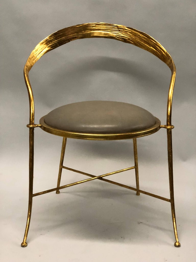 Pair of Italian Mid-Century Modern gilt iron lounge chairs or armchairs by Giovanni Banci.  The chairs feature strong but delicate ironwork and design influenced by a Modern Neoclassicism and Italian design. The backrest is daringly curved, the