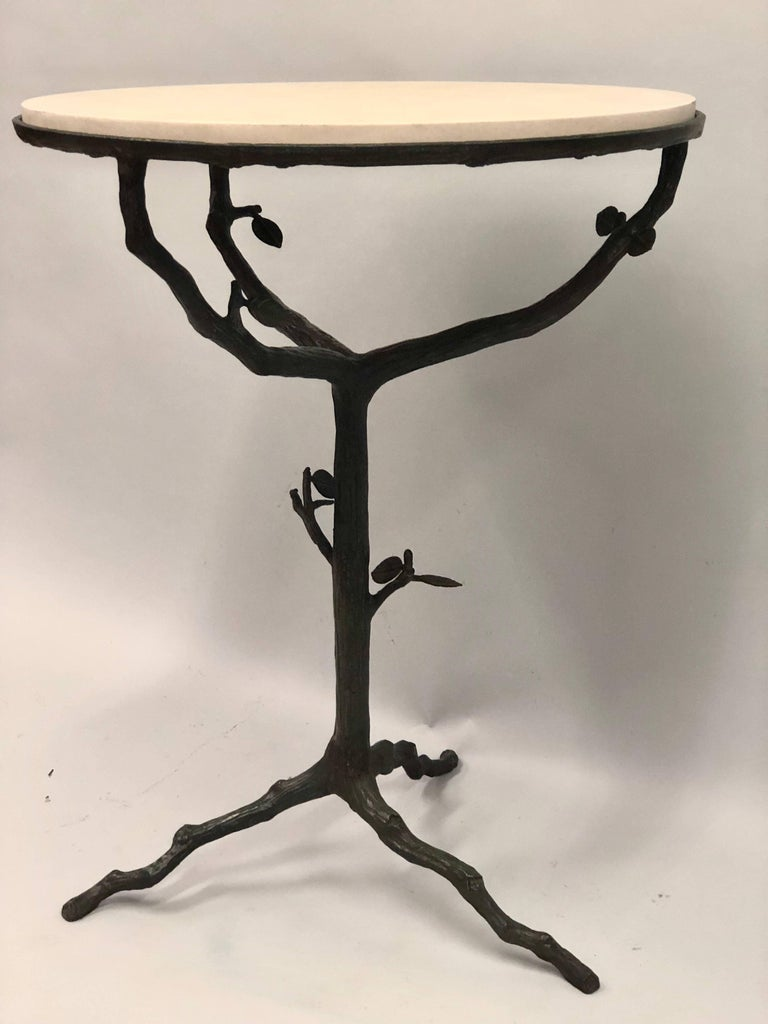 Elegant pair of French Mid-Century Modern side or end tables in bronze in the style of Alberto and Diego Giacometti.  The pieces feature an organic form tripod base and stem with twig and leaf decoration characteristic of the Giacometti's work