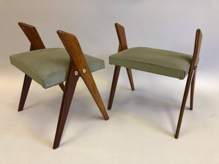Rare and exceptional pair of Italian Mid-Century Modern wood stools or benches featuring pairs of angled and tapered saber legs that unite to support seats. Solid brass pins and leg detailing complete the composition.  Seats coverings are original