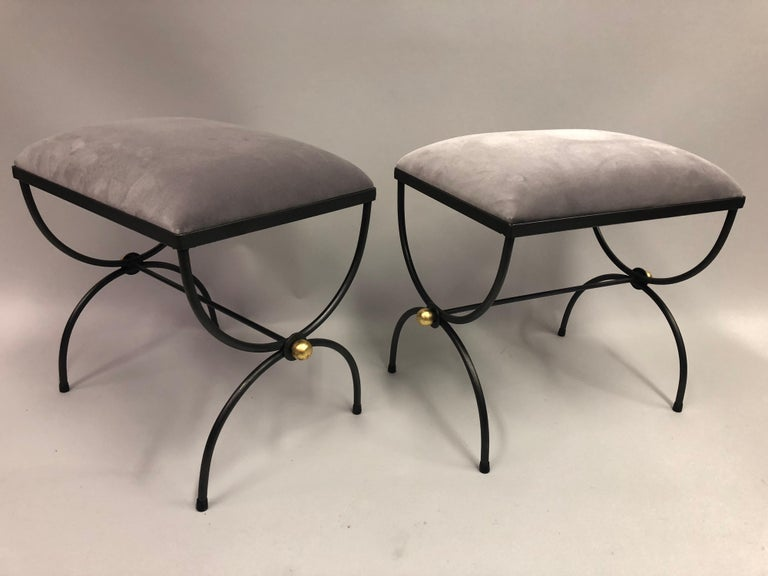 Elegant and timeless pair of French Mid-Century Modern neoclassical hand wrought iron and gilt benches or stools attributed to Maison Baguès. The pieces are in a classic Curile / X-Frame Design and finished with gilt iron ball finials at the