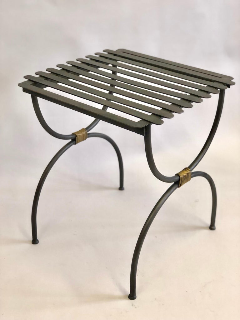 3 Pairs of French X-form iron side tables / luggage racks from the Mid-Century Modern period in the style of Jean Michel Frank. The pieces, in matte black patina, are in the curile form with gilt iron wrappings uniting upper and lower halves.