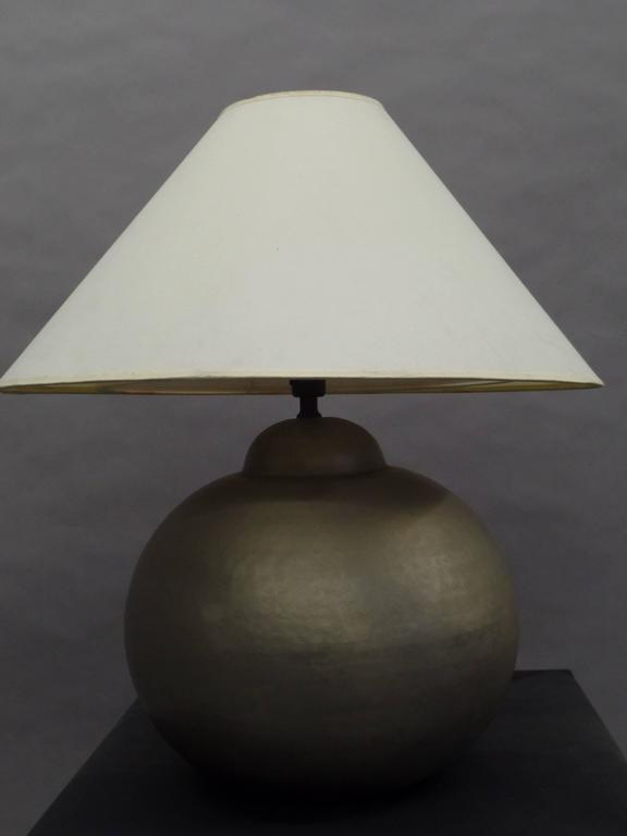Elegant pair of French Mid-Century hand-hammered solid brass table lamps, matte nickeled and in a circular form with a sober, modern spirit. 