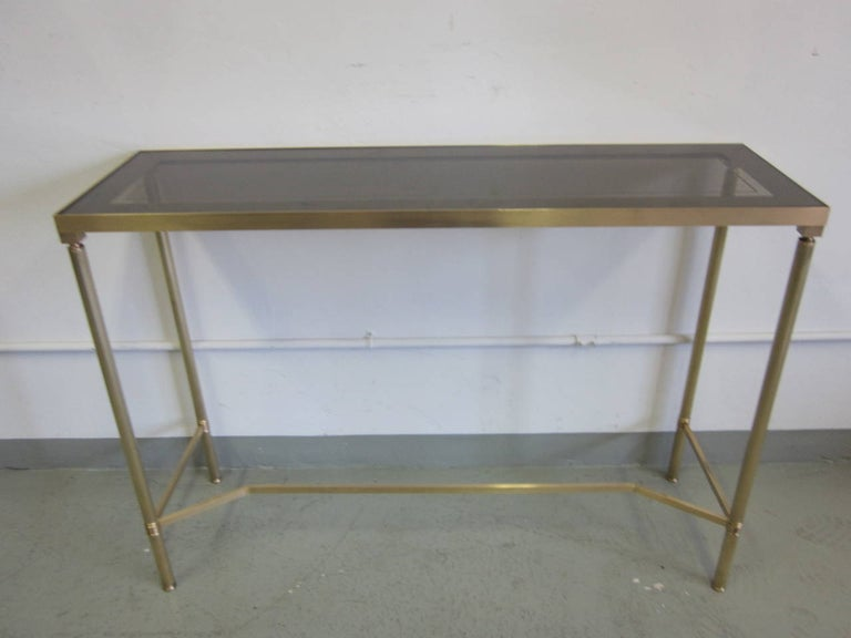 Sober, French Mid-Century Modern neoclassical console attributed to Maison Baguès in solid brass with a smoked glass top partially reverse painted to form a wide rectangular band in a muted grey around the edges.  References: Maison Jansen.