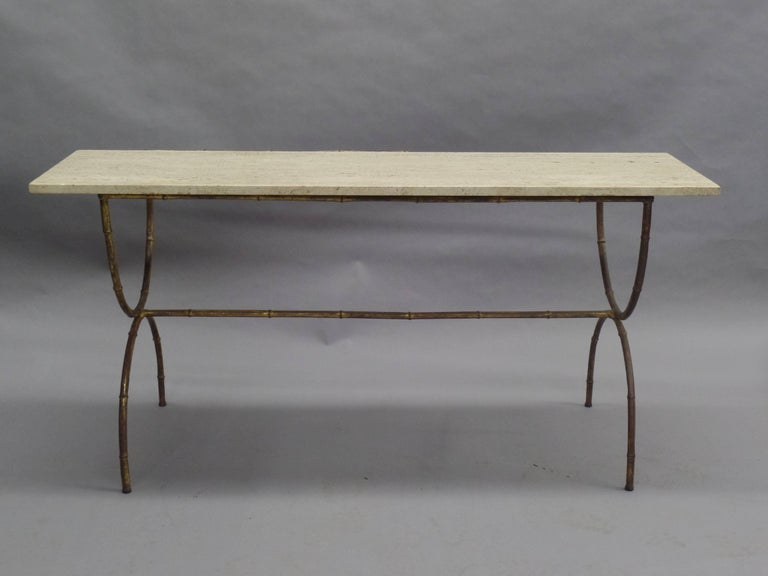 Elegant French Mid-Century Modern Neoclassical sofa table, console or vanity in gilt faux bamboo by Maison Baguès. The table is designed in a modern neoclassical curile form with X-frame legs and a center stretcher uniting the legs. Top of calicatta