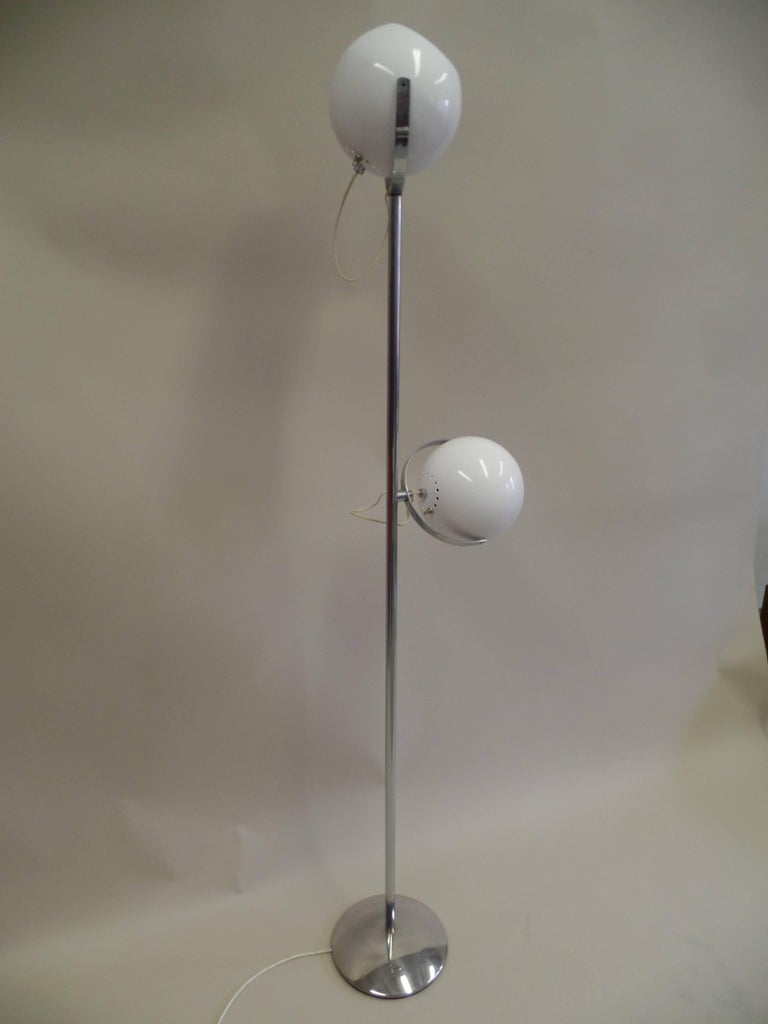 Iconic pair of Italian Mid-Century Modern / Minimalist / Space Age standing lamps by Reggiani in perfect color balance with nickel bases and stems and white enameled steel reflectors.  Each reflector articulates / rotates to direct light up, down